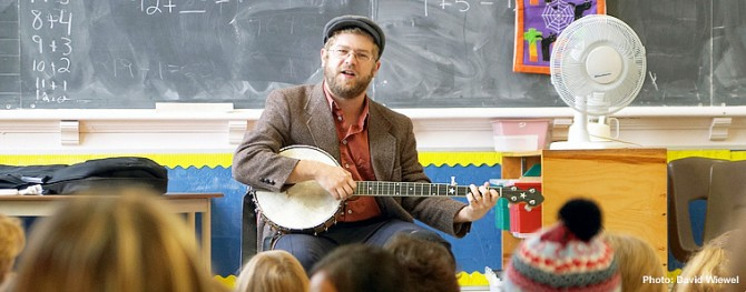 Old Man Luedecke with banjo in classroom